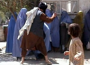 Taliban beating woman in public for immodesty.